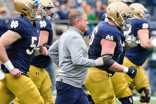 Notre Dame Fighting coach Brian Kelly runs onto the field for the of the 2018 Blue-Gold Game at Notre Dame Stadium.