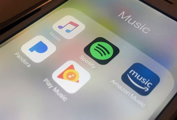 This Jan. 28, 2018, file photo shows music streaming apps clockwise from top left, Apple, Spotify, Amazon, Pandora and Google on an iPhone in New York.