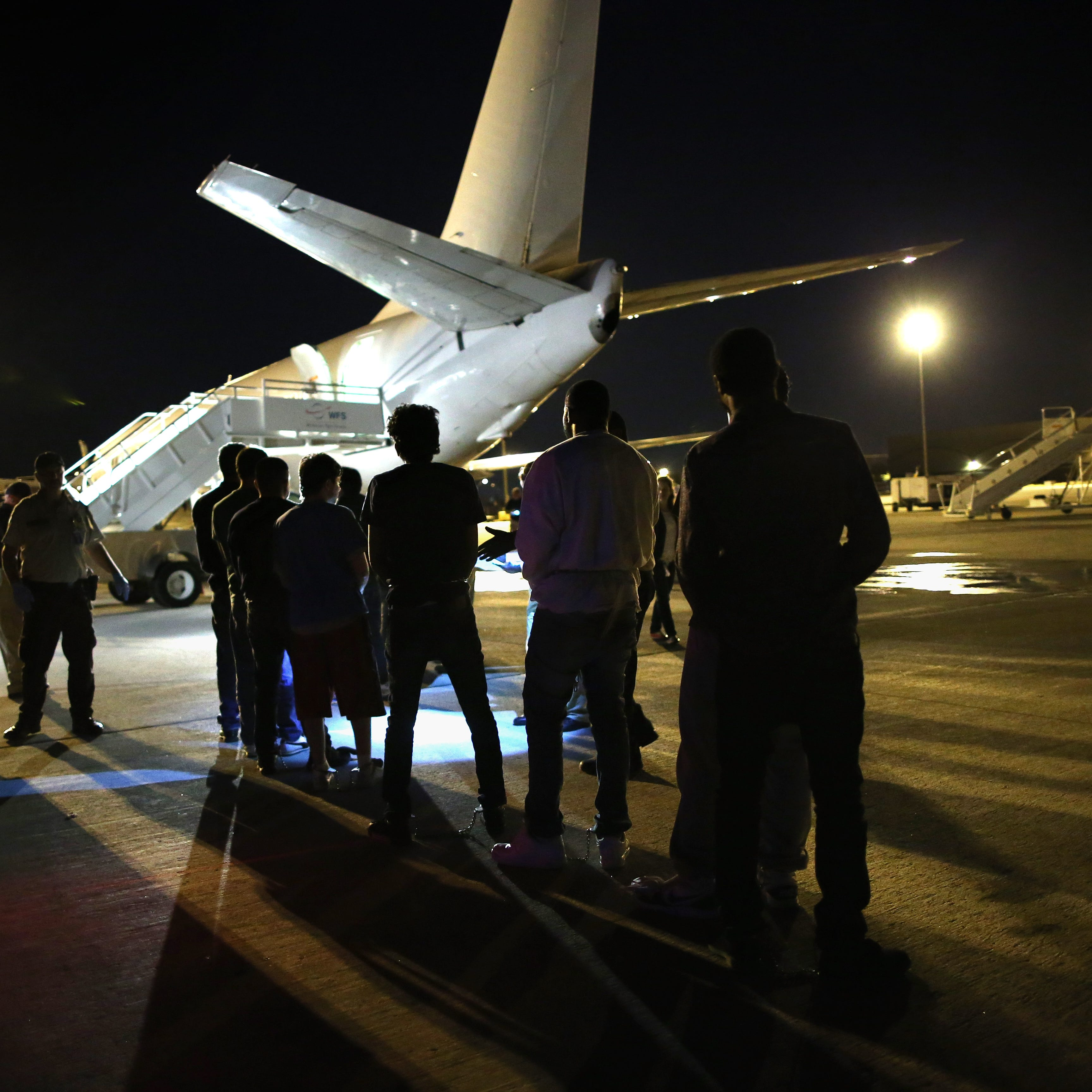 Undocumented immigrants wait to be loaded onto an Immigration and Customs Enforcement charter jet early on October 15, 2015, in Mesa, Ariz.