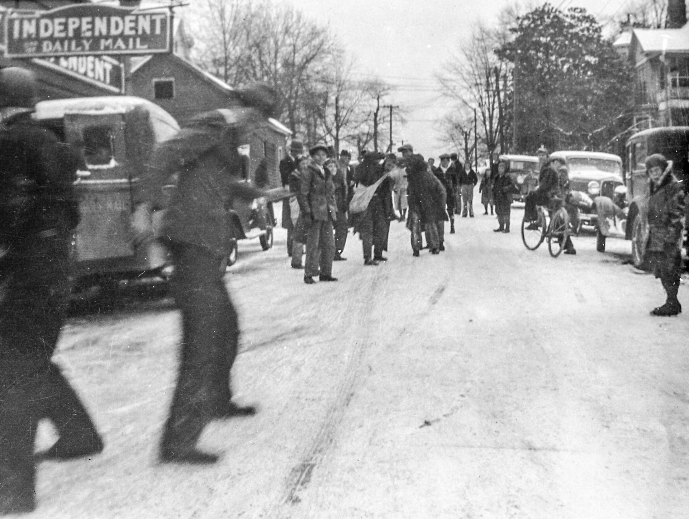 People walk around in the snow covered street along East Market Street in front of the Daily Mail and Independent in downtown Anderson in 1945.