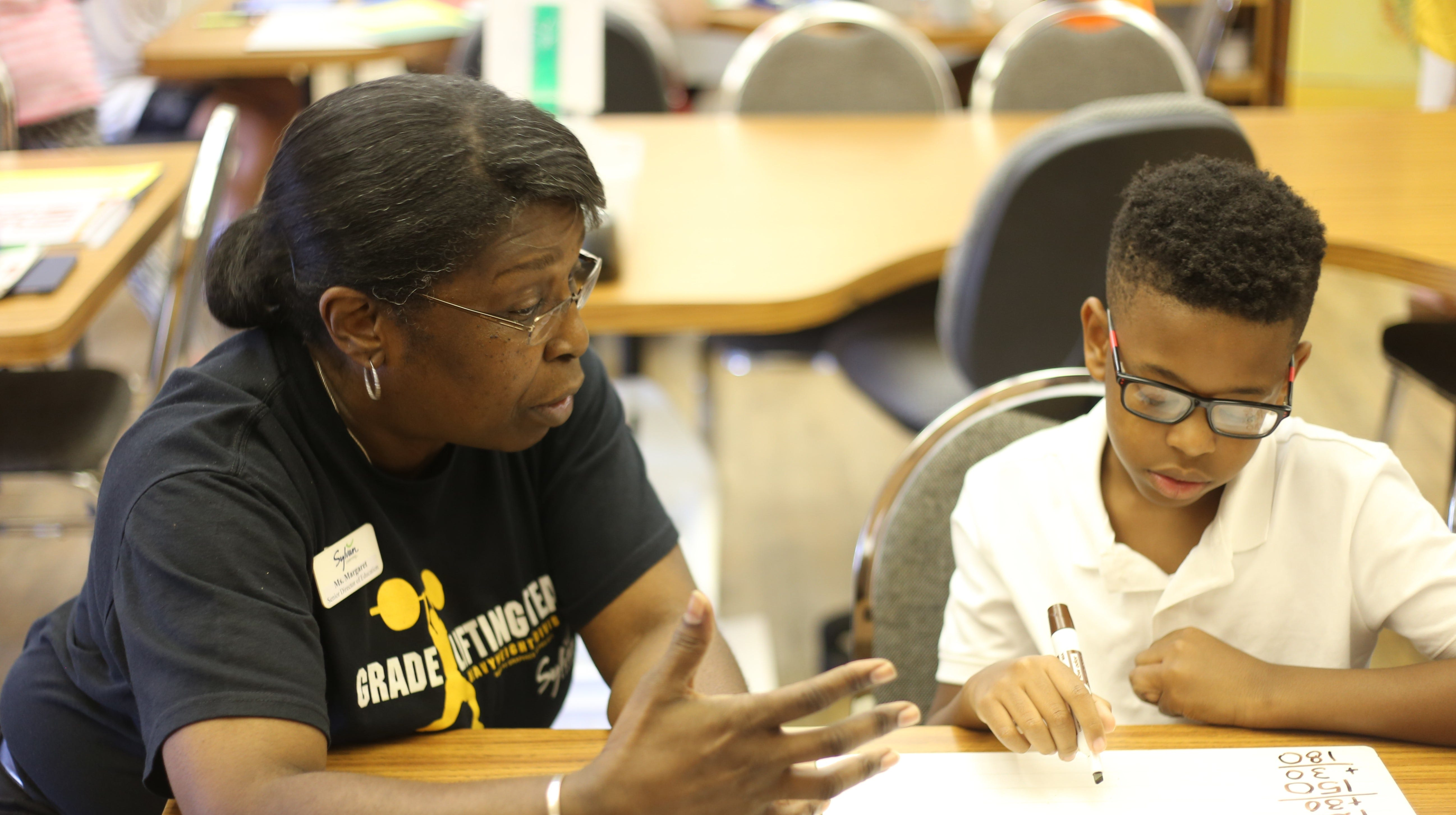Kameron Arceneaux receives math assistance from Margaret Maffett Thursday at Sylvan Learning Center of Alexandria, which recently relocated to Canterbury Drive.