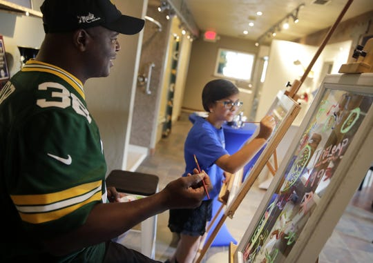 Packers Hall of Famer LeRoy Butler talks with Sydney Berndt, 12, as they paint together as part of the Windows for a Cause kickoff event Thursday at Tundraland Home Improvements in Kaukauna.