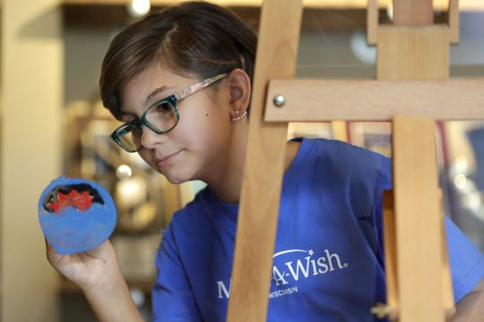 Sydney Berndt of Hobart paints a window Thursday at Tundraland Home Improvements in Kaukauna. The window is one of 1,500 that are planned to be painted Saturday and Sunday at the Fox Cities Exhibition Center in Appleton. Some of the windows then will be auctioned off to benefit Make-A-Wish Wisconsin.
