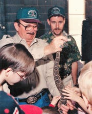 Snake-hunters Tom Wideman, left, and his son, Gary, show off rattlers to Boy Scouts in 1994.
