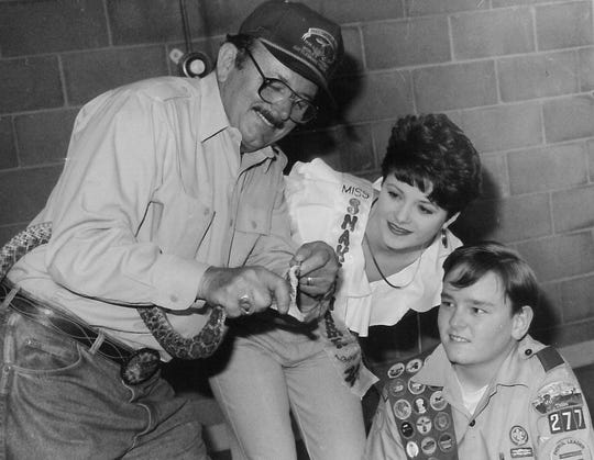 Tom Wideman shows off a rattlesnake to 1992 Miss Snake Charmer Paige Allen and Boy Scout Trevor Rose during a 1994 rattlesnake safety demonstration at Southern Hills Church of Christ.
