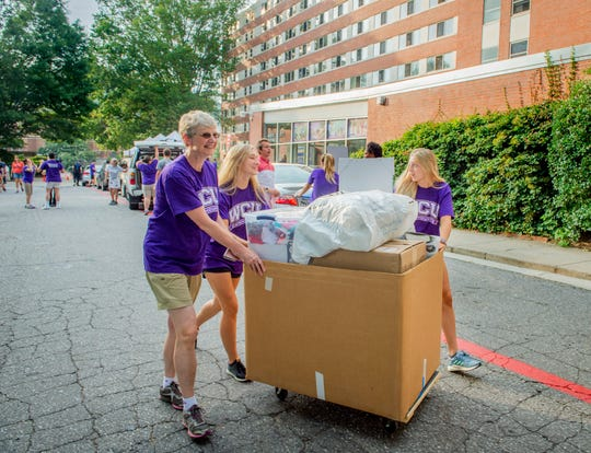 In this file photo, Western Carolina University Interim Chancellor Alison Morrison-Shetlar, left, joins student volunteers in wheeling a load into Scott Residence Hall on Move-In Day last year. Like all colleges in the UNC system, WCU has taken a financial hit from the COVID-19 pandemic.
