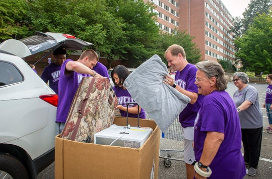 Western Carolina University men's head basketball coach Mark Prosser, center right, and assistant basketball coach Brigham Waginger, center left, get in on the action helping incoming freshmen at the university's Move In Day, Friday. More than 1,500 WCU students, faculty and staff banded together to help the university's incoming freshmen move into their residence hall rooms. Classes start Monday.