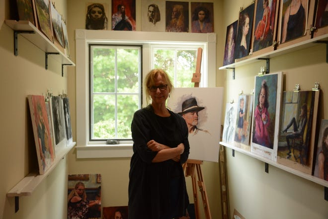 Artist Nan Sherry stands among her paintings.