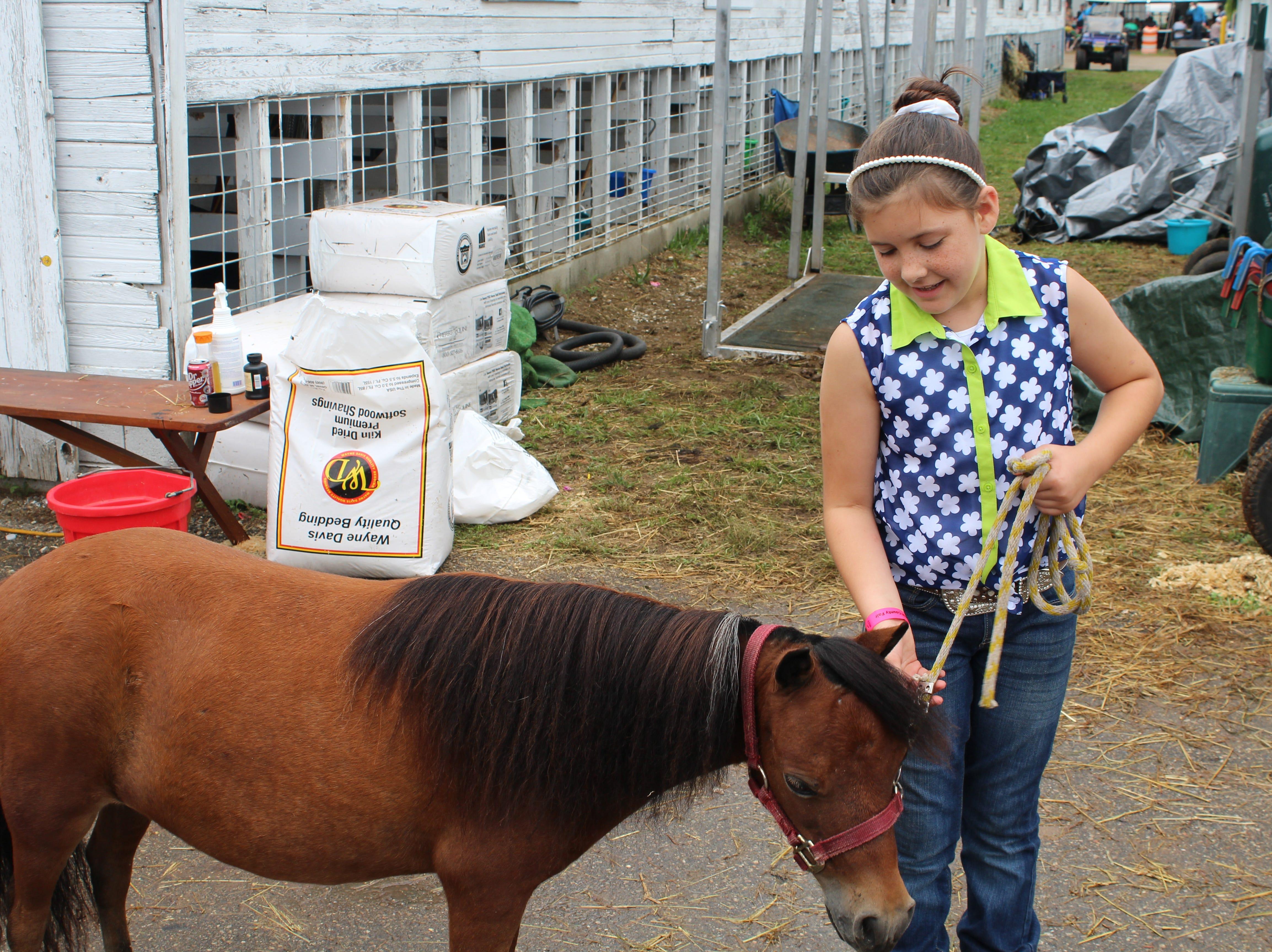 Ava Brodock, 9, shows off her miniature horse, Rhuna at the Calhoun County Fair.