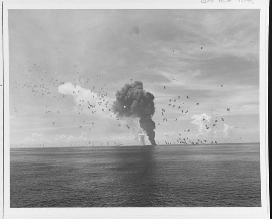 Afire and sinking after a Kamikaze hit off Leyte, 1 November 1944. Another Japanese plane is burning on the water to the left of the sinking destroyer. Note heavy anti-aircraft fire.