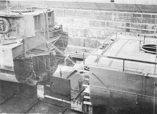 7 October 1943 - ABNER READ in dry dock at Puget Sound Navy Yard showing temporary steering gear. Prefabricated stern section is in foreground.