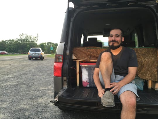 Elias Landsman of Asheville, N.C., sits in the back of his vehicle Aug. 16, 2018, wondering what to do next after learning Phish's Curveball festival was canceled.