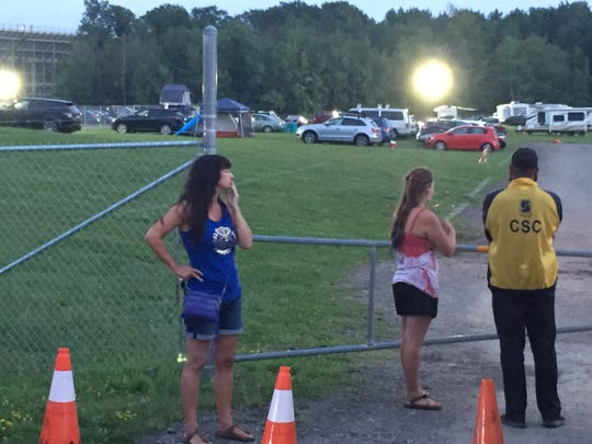 Fans stand outside the gates of Phish's Curveball festival trying to figure out what to do next after the event was canceled Aug. 16, 2018.