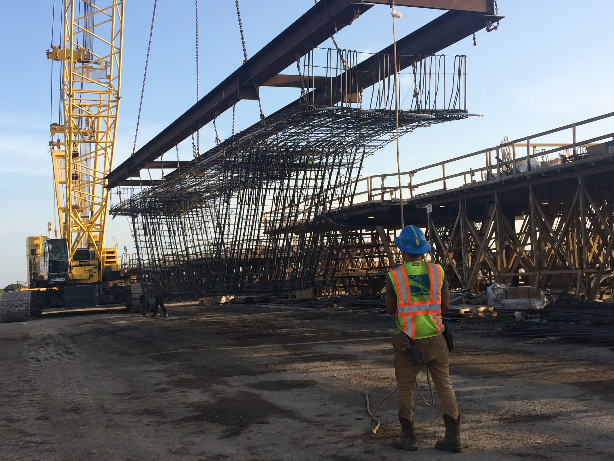 A Flatiron/Dragados worker guides an unfinished bridge segment at the Harbor Bridge pre-cast yard in Robstown. Pieces of what will be the new bridge are being constructed here.