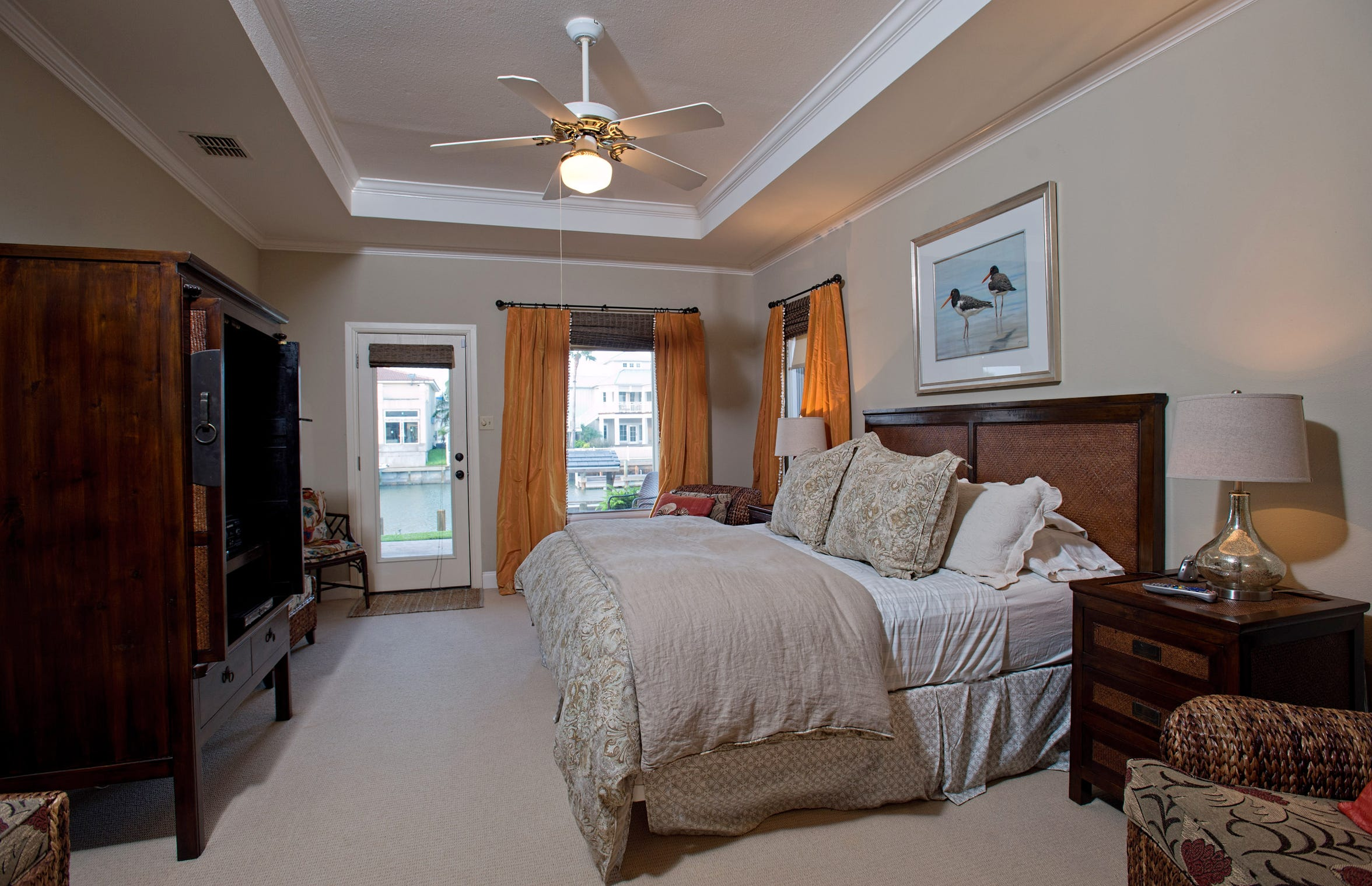 The first floor master bedroom features a water views and deck access plus an attractive recessed ceiling.