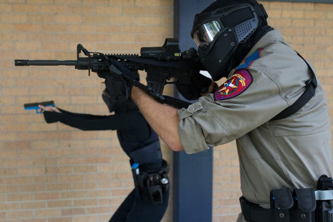A Texas Department of Public Safety trooper and a CCISD police officer walk down a hallway during an active-shooter drill at the old Cullen Middle School.