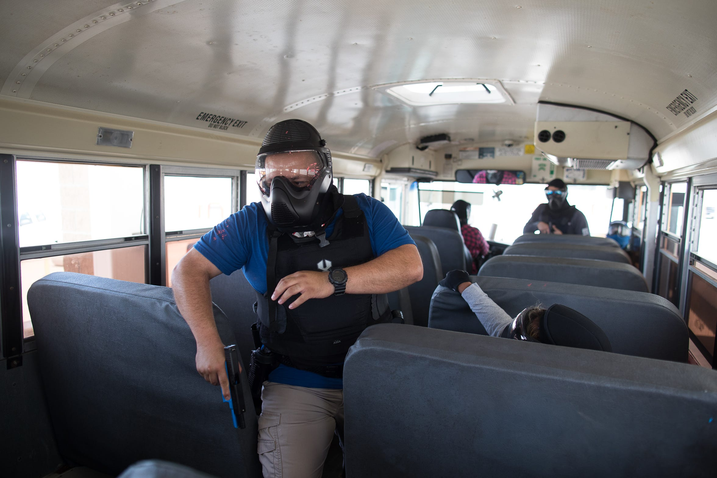 A Corpus Christi independent School District police officer walks through a school bus during an active-shooter drill two weeks before school starts.