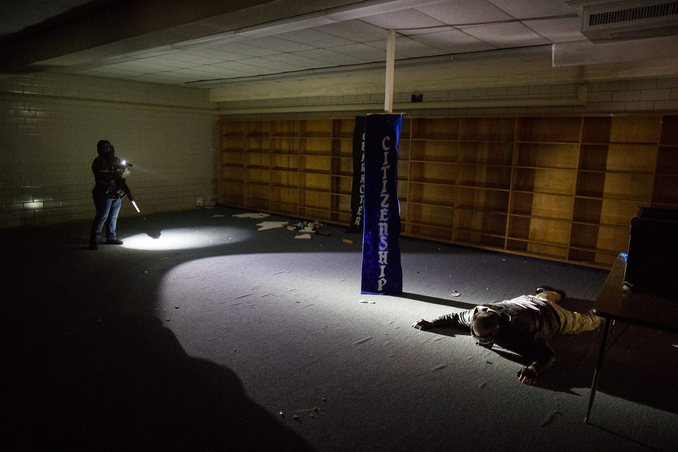 A CCISD police officer shines a light on a suspect in a dark room during an active-shooter drill at the old Cullen Middle School.