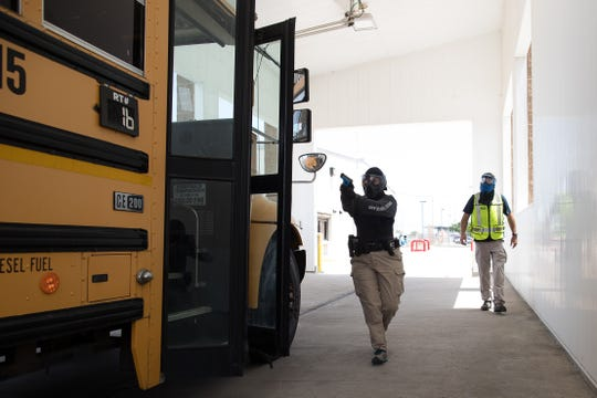 A Corpus Christi independent school district police officer approaches a school bus with gun pointed during an active shooter drill two weeks before school starts.