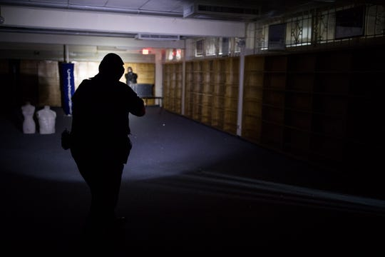 A CCISD police officer shoots at target in a dark room during an active shooter drill at the old Cullen Middle School before the start of the new school year.