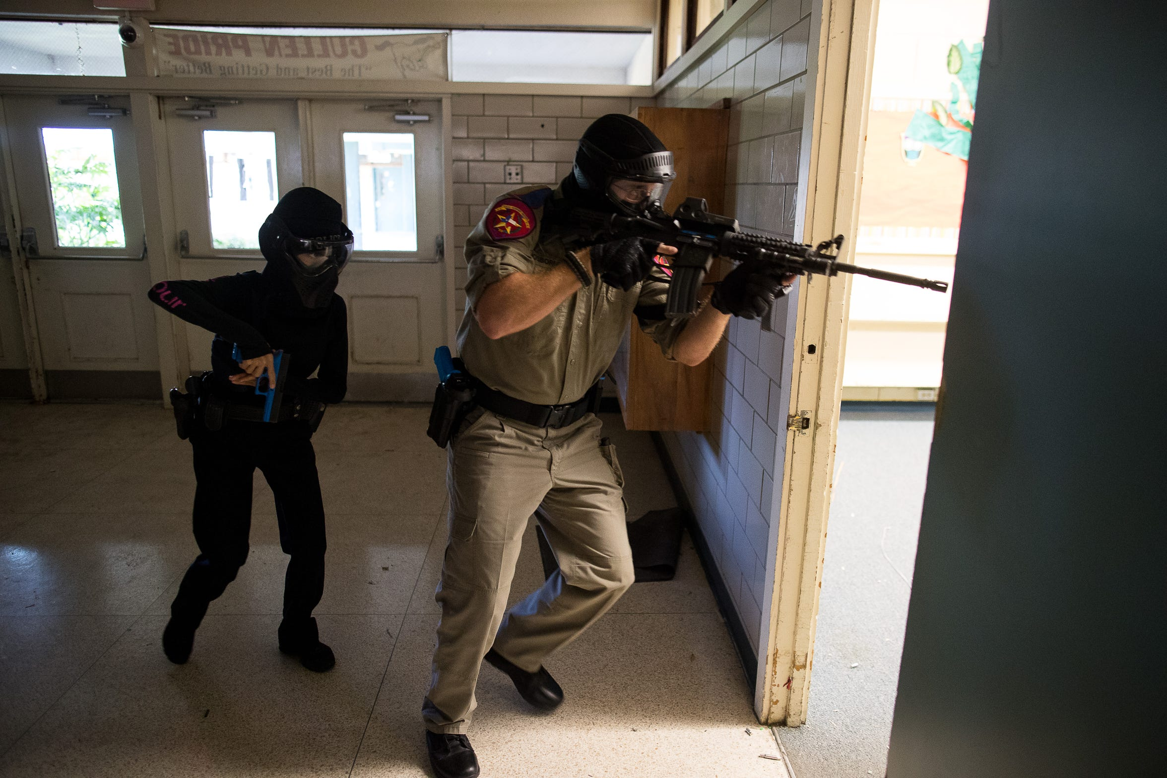 A Texas Department of Public Safety trooper and CCISD police officer enter a room during an active-shooter drill at the old Cullen Middle School.