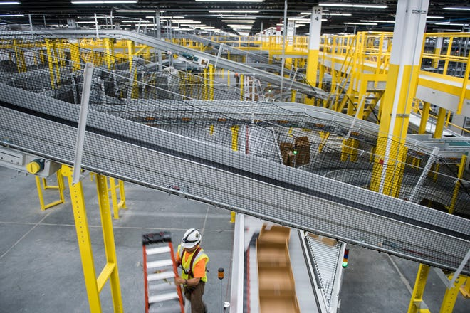 Boxes move across the line as construction ensues at the new Amazon fulfillment center Friday, Aug. 17, 2018 in West Deptford, N.J.