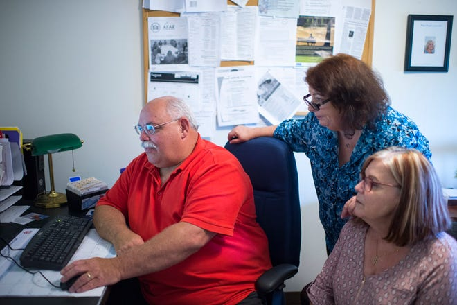Ed Brazell, founder of The Silent Epidemic in Gibbstown, (from left) Colleen Howard and Kathleen Frazer of Parent-to-Parent in Marlton, review a new web portal shared by eight South Jersey nonprofits. The site is used to review applications for rental assistance at sober living houses.