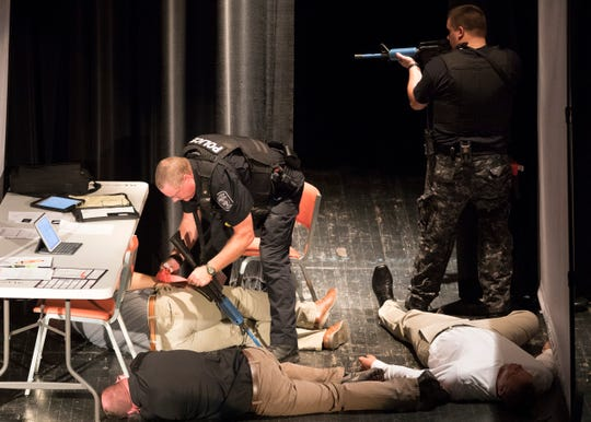 Officers secure the scene and check for survivors during an active shooter presentation presented to local businesses Thursday afternoon at Chillicothe's Majestic Theatre.