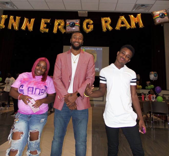 Casandra Jeffers and Khalil Cromwell (right) pose with keynote speaker Michael Williams, Jr. at the 2018 Annual Youth Conference held at Community Access Unlimited this week.