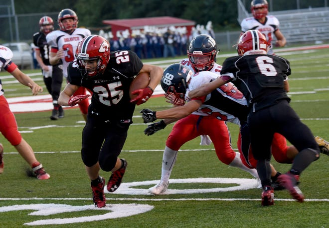 Coshocton's Braydon Tomak (25) carries the ball as teammate Andrew Kittell blocks in a game last season. Tomak and Kittell are among the seniors aiming to help Coshocton rebound from a 2-8 season.
