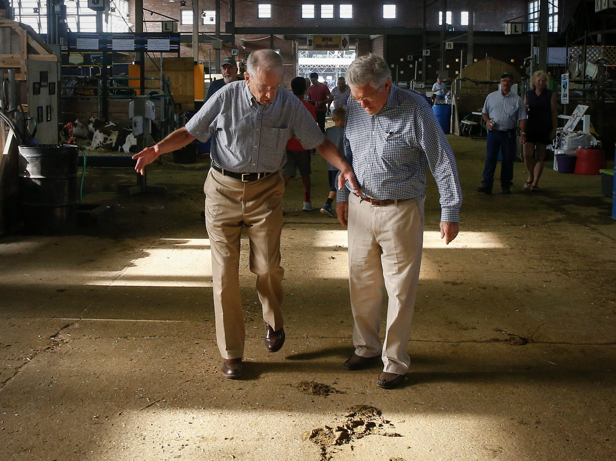 U.S. Sen. Charles Grassley (R-Iowa), left, warns Fred Barnes, a reporter at the Washington Weekly Standard, about a cow pie in the hallway of the dairy barn on Friday, Aug. 10, 2018, at the Iowa State Fair in Des Moines.