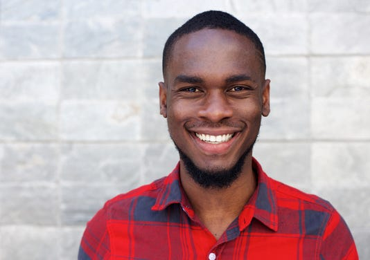 Happy Young African Man Smiling Against Gray Wall