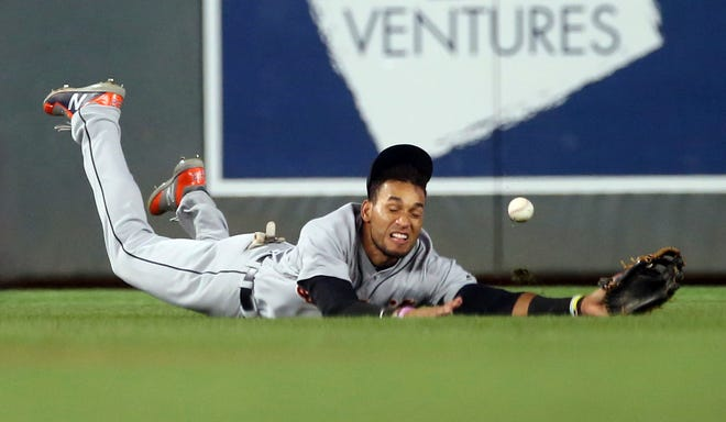 Detroit Tigers center fielder Victor Reyes makes a futile dive for a hit by Minnesota Twins' Logan Forsythe during the sixth inning of a baseball game Thursday, Aug. 16, 2018, in Minneapolis.
