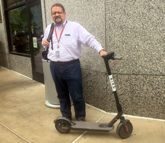 Joe Guziewicz of Grosse Pointe with a Bird scooter in downtown Detroit on Wednesday, August 16, 2018.