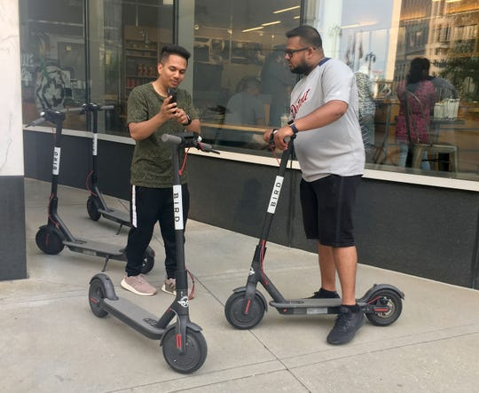 Jamil Ahmad of Troy, left, and Sabir Hussain of Sterling Heights, with Bird scooters in downtown Detroit on Wednesday, August 15, 2018.