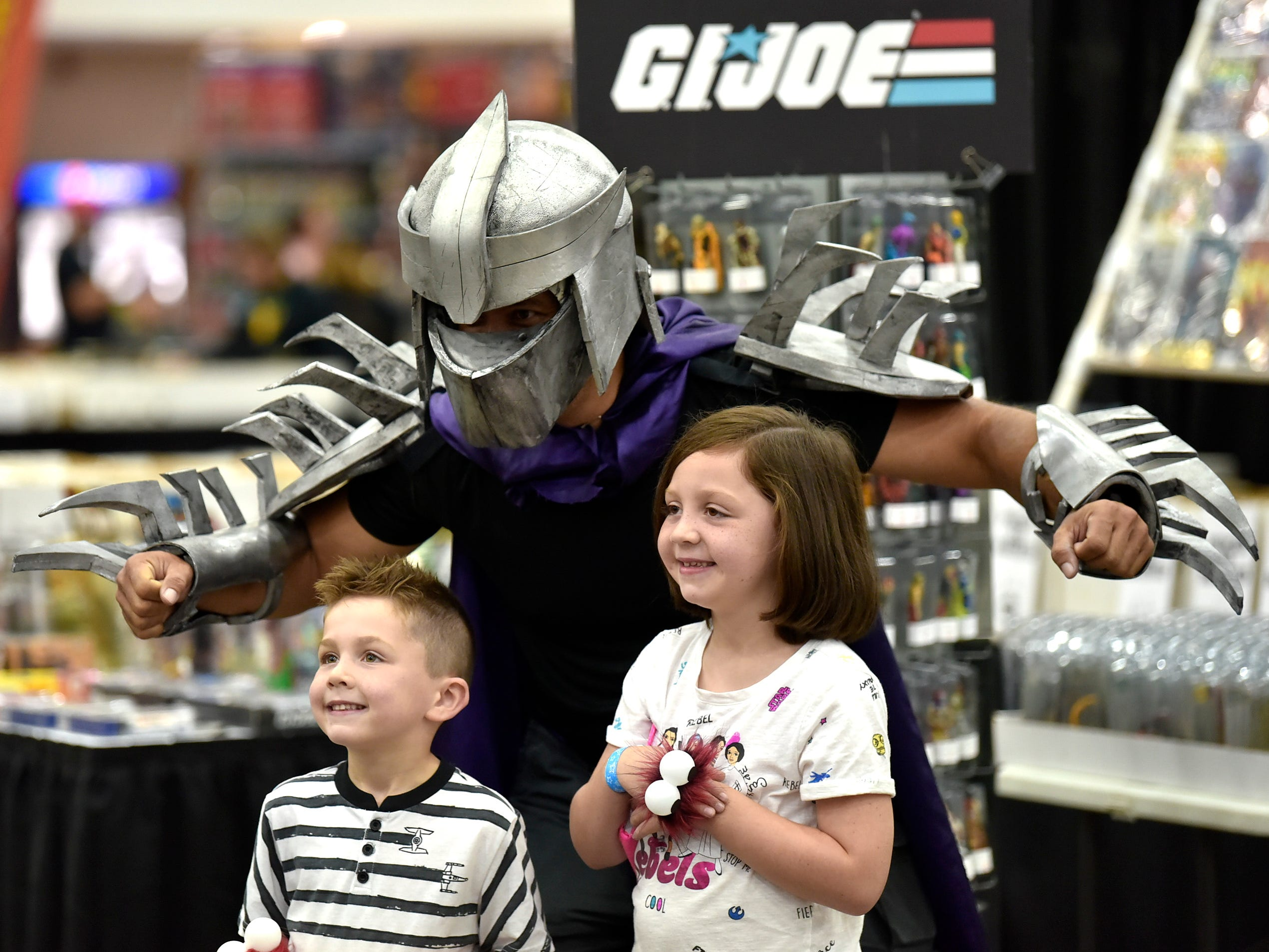 "John McKee, left, 45, of Ferndale portrays ""The Shredder"" from the Teenage Mutant Ninja Turtles series while  posing with Aaden Jesue, 5, and sister, Khloe Jesue, 8, of Taylor."