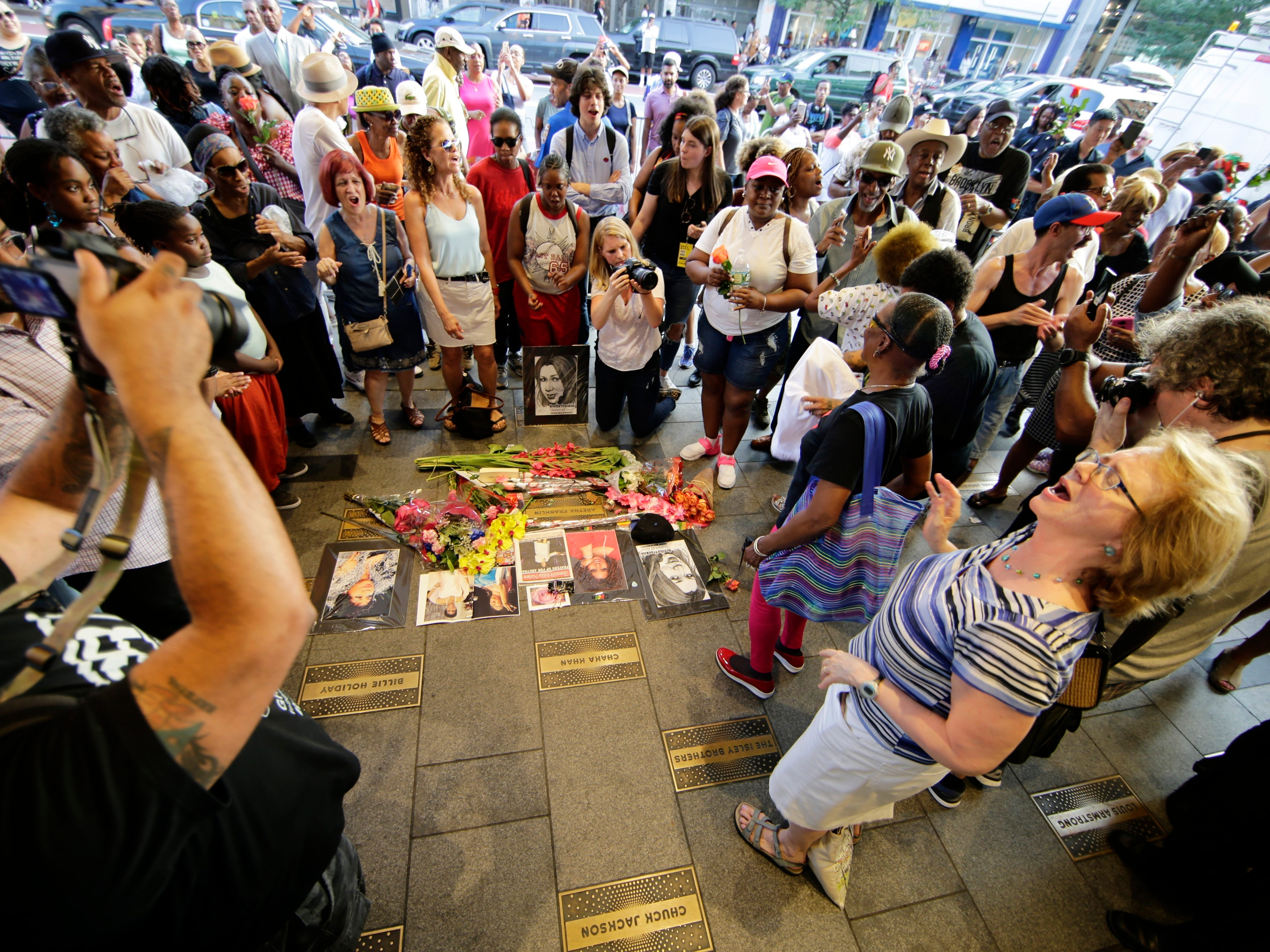 People dance and sing at a makeshift memorial for singer Aretha Franklin outside the Apollo Theater Thursday, Aug. 16, 2018, in New York. Franklin died in her home in Detroit at age 76 from pancreatic cancer. (AP Photo/Frank Franklin II)