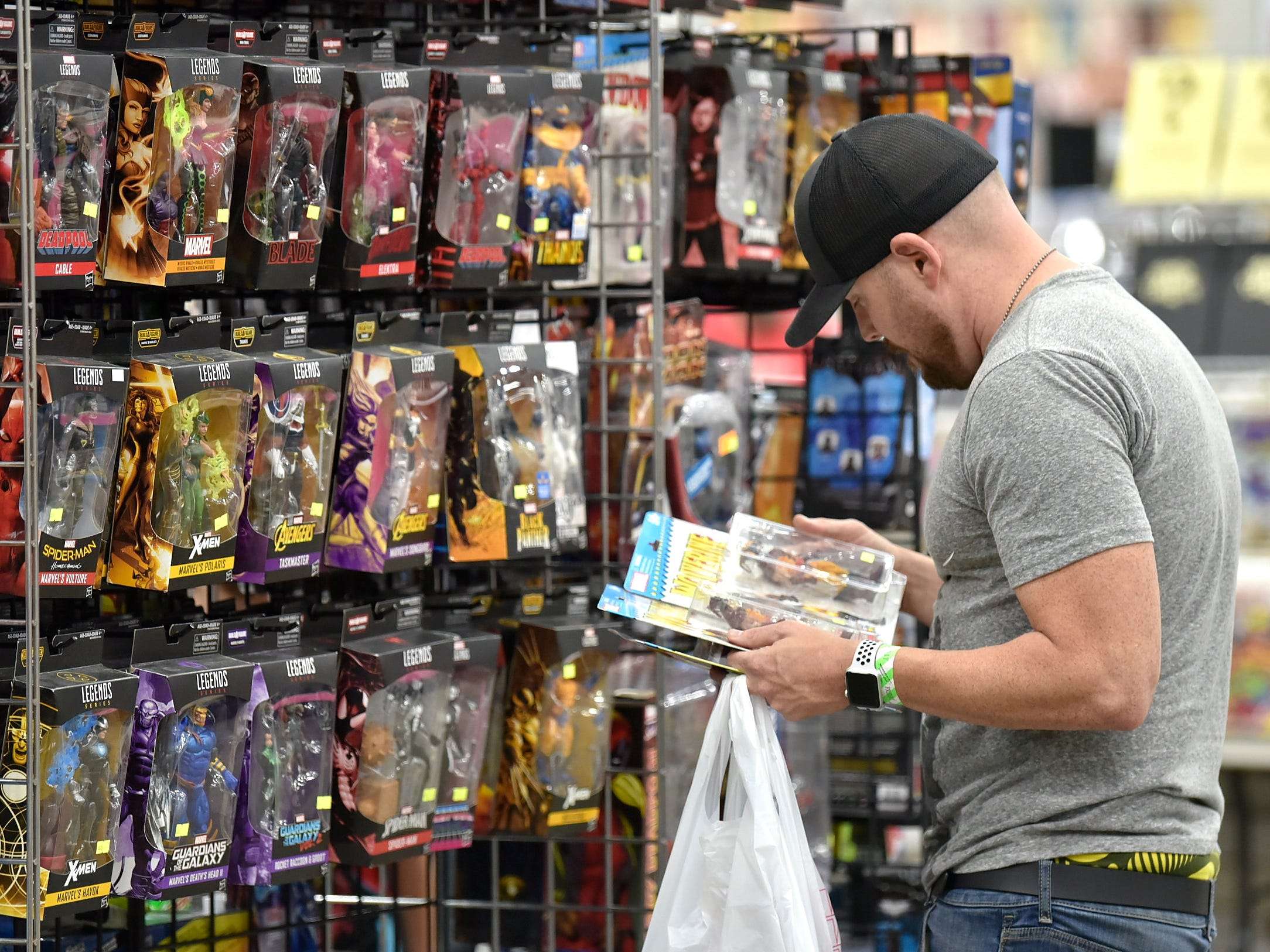 "Rodney Elswick, 41, of Garden City peruses Marvel Legends actions figures at the ""My Wife Is Going To Kill Me"" podcast booth."