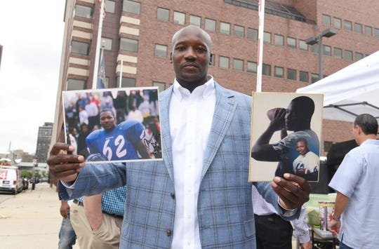 Aaron Salter  shows off his Kettering High School football photographs from 1994 after he was exonerated and released from prison Friday in Detroit after serving 15 years  for a murder he didn't commit.