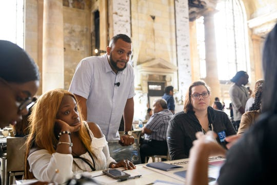 Shawn Wilson (standing), a manager with Ford Fund, engages a tableful of young entrepreneurs as they brainstorm ideas for   developing workspaces in the Michigan Central Depot train station, Friday.