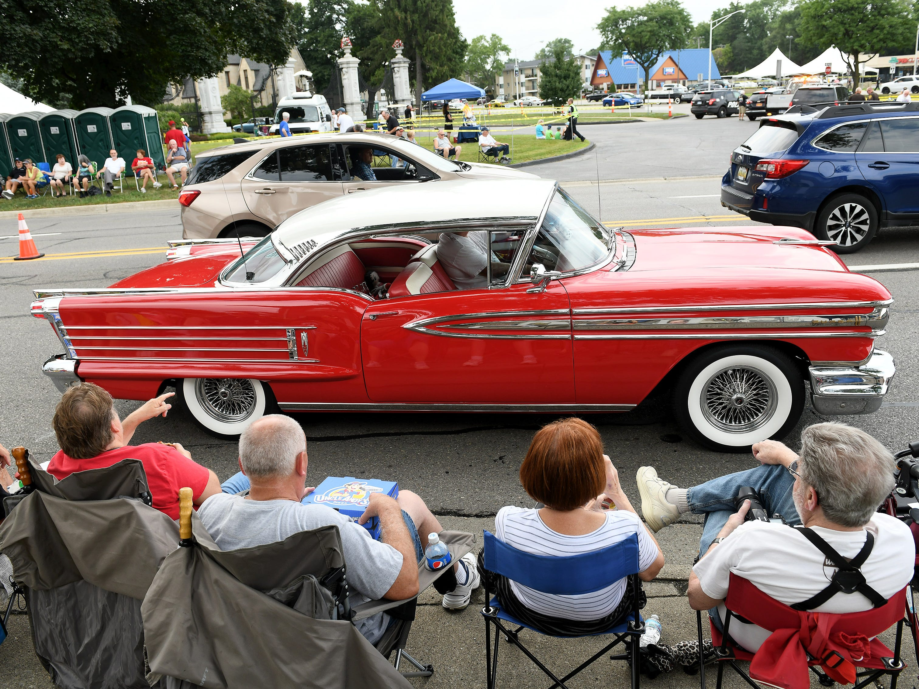 Spectators watch a classic Oldsmobile roll by on Woodward Friday night in Berkley.