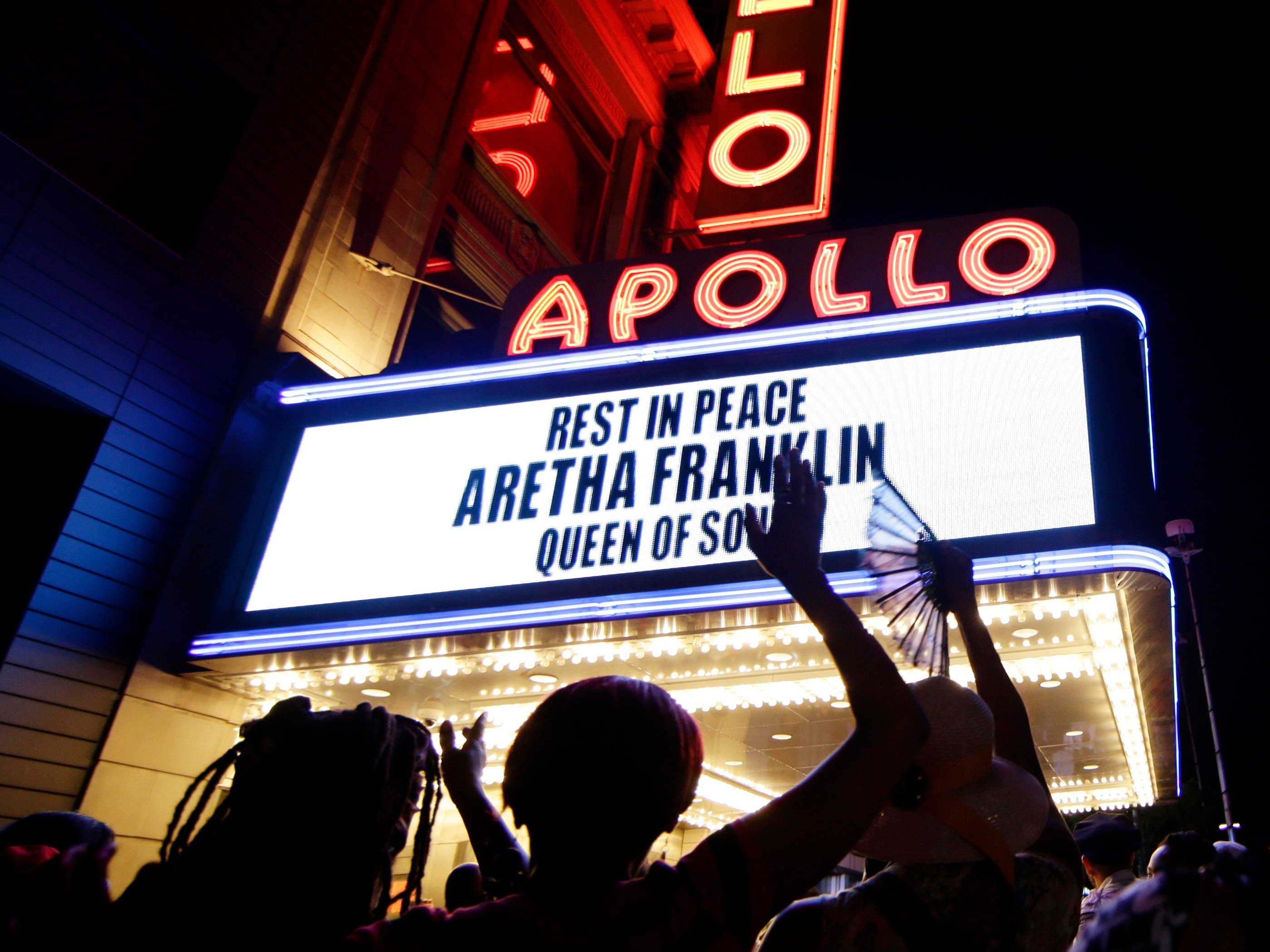People gather at a makeshift memorial at the nameplate for singer Aretha Franklin outside the Apollo Theater Thursday in New York.