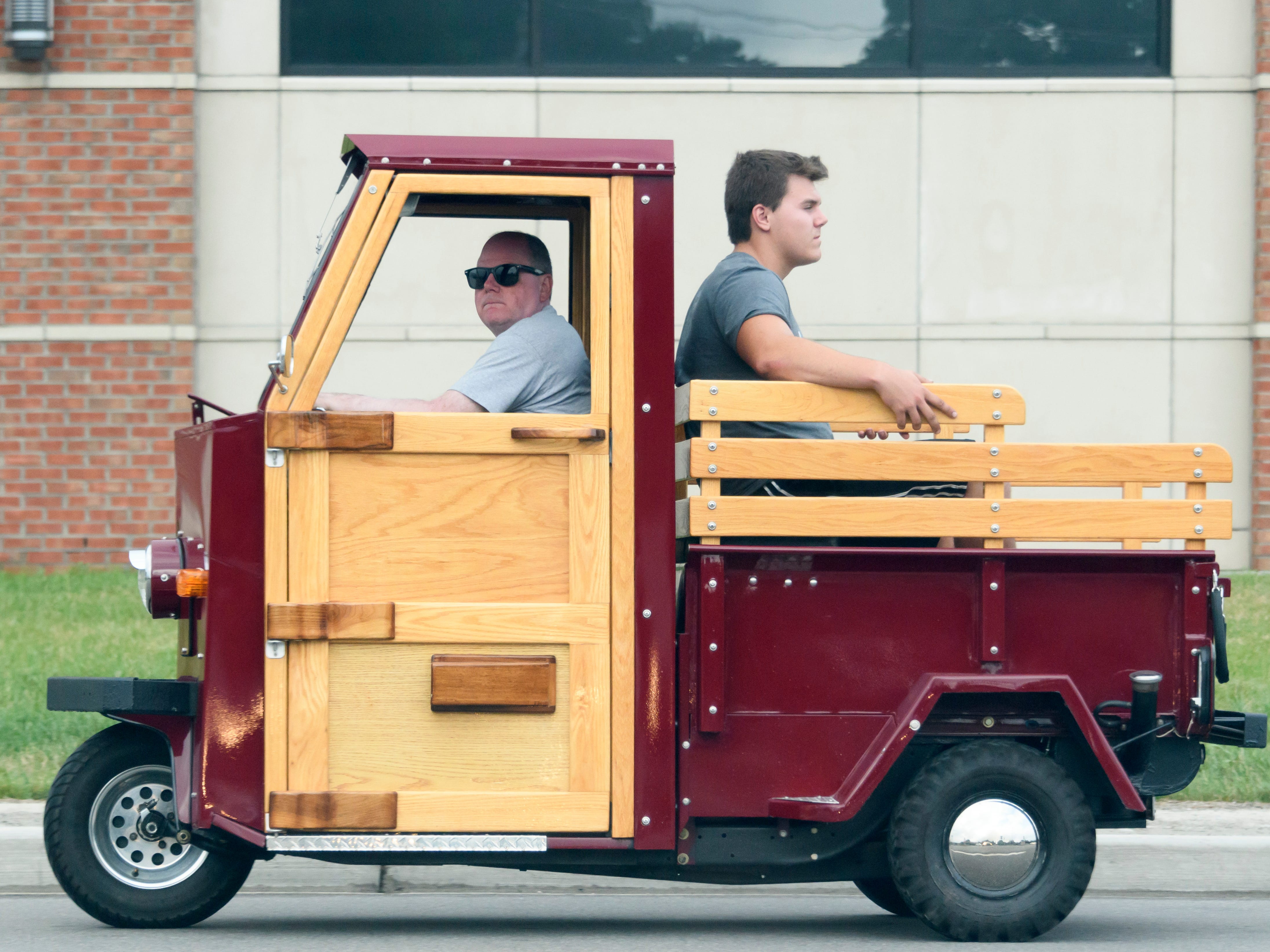 Frank Pavia of Plymouth drives his 1977 Cushman Truckster with passenger Brand Chanler Thursday along Woodward near Normandy in Royal Oak in preparation for the Dream Cruise.