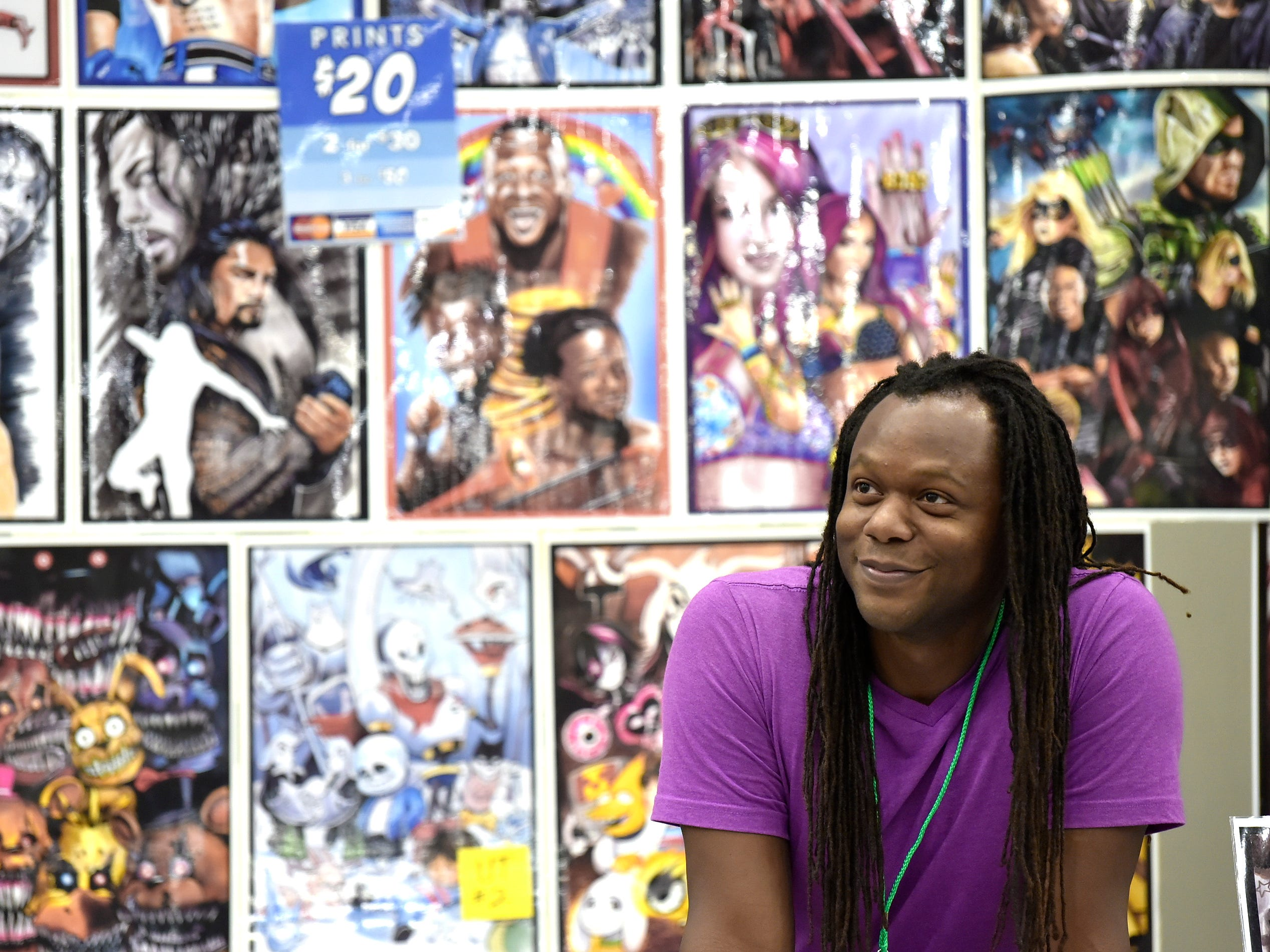 Comic book artist A.J. Moore of San Antonio, Texas chats with customers in front of his creations.