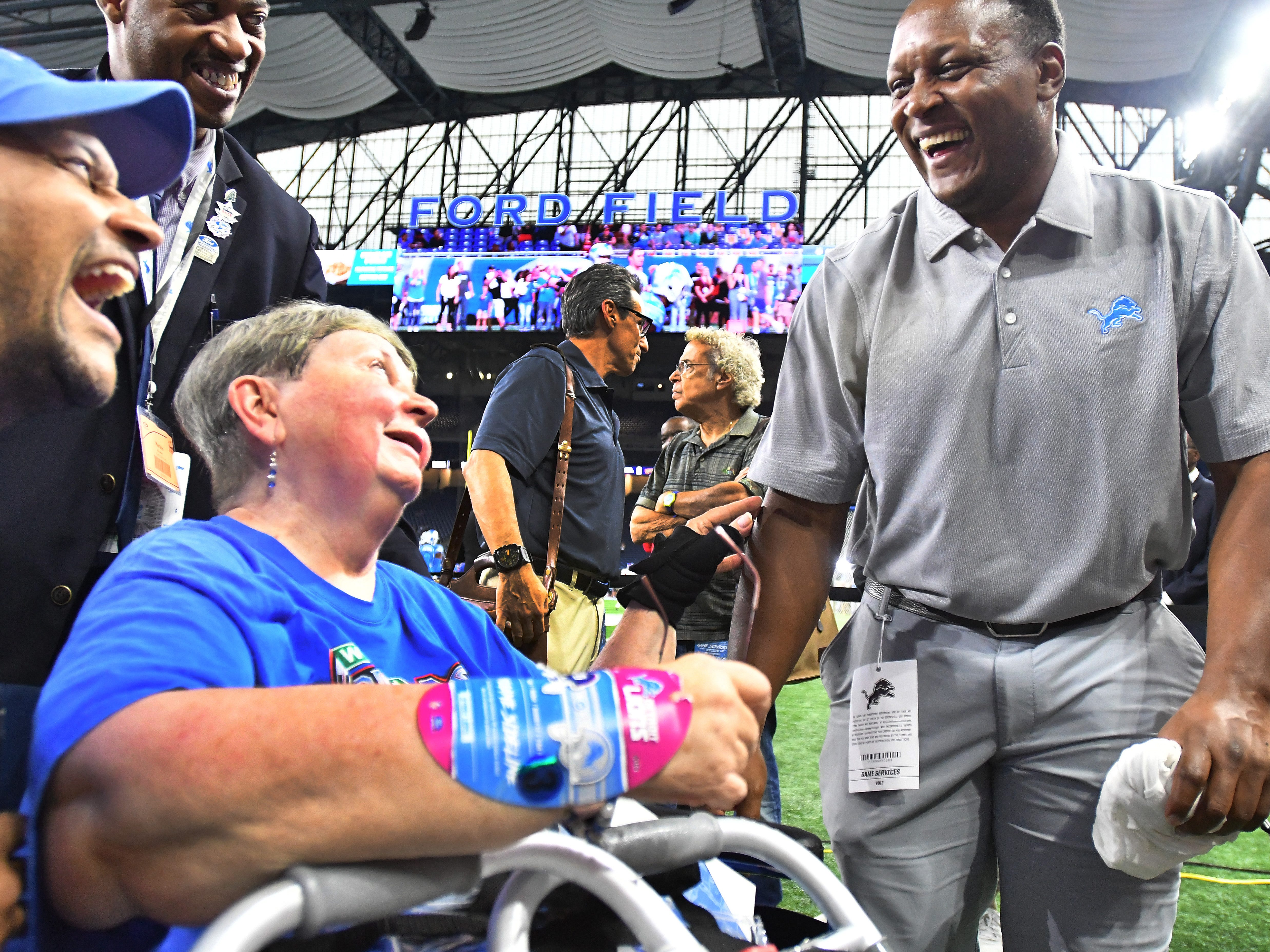 Actor Keegan-Michael Key and his mother, Patricia Walsh share a laugh with NFL Hall of Fame running back Barry Sanders on the field before the Detroit Lions and the New York Giants play at Ford Field in Detroit, Michigan on August 17, 2018.