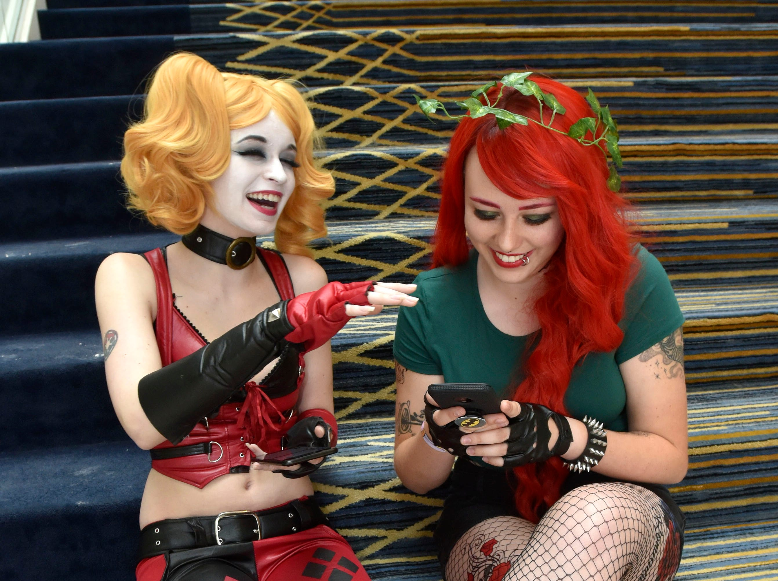 "Elle Jones, left, of Mount Clemens portraying ""Harley Quinn"" shares a laugh with fellow 20-year-old Danielle Lang of Warren, dressed as ""Poison Ivy"" at Michigan Comic Con at Cobo Center, Friday, Aug. 17, 2018. The event continues through Sunday."