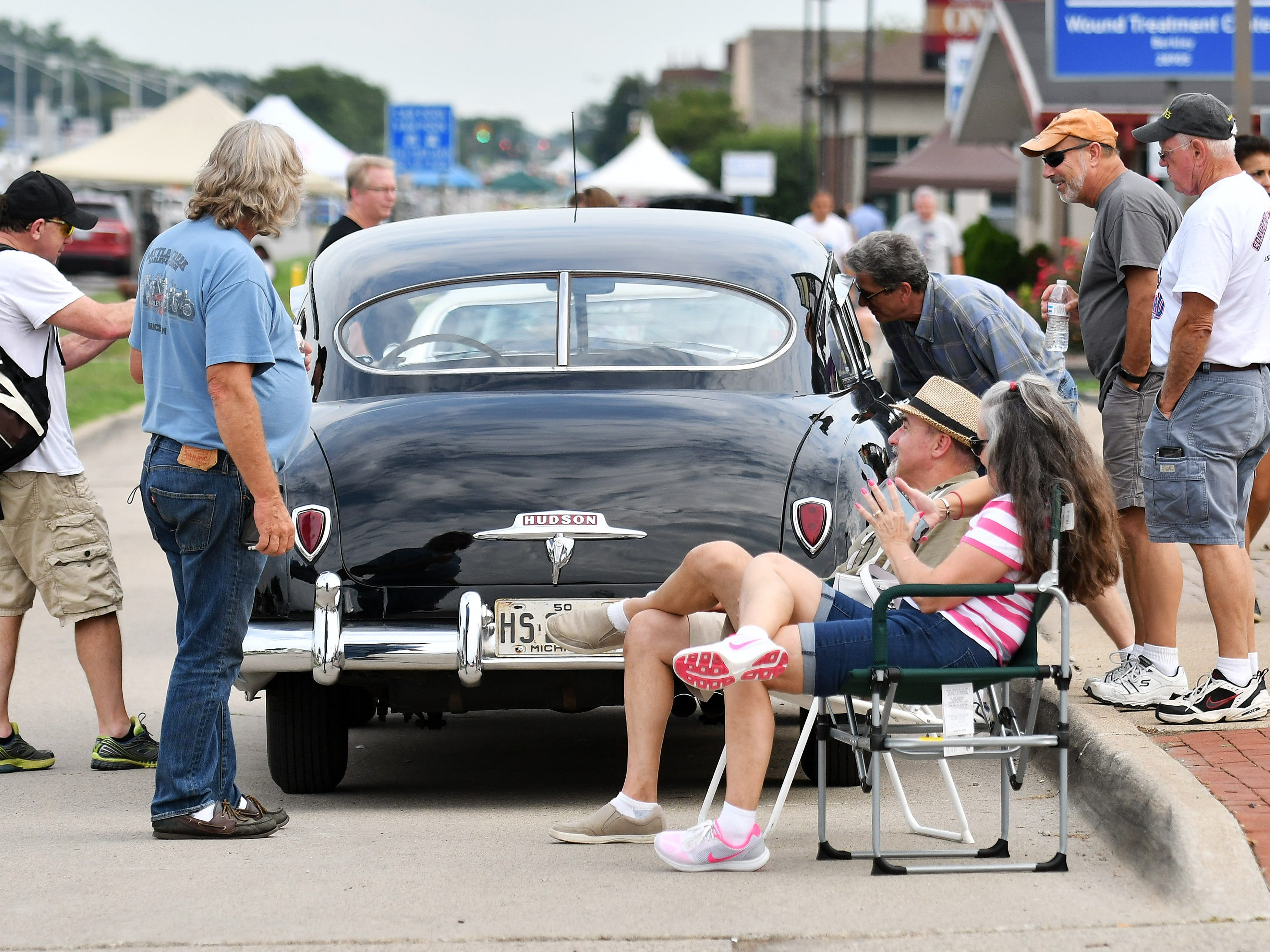 People stop and check out the 1950 Hudson Super Six belonging to Heidi and Duane Sabella of New Baltimore, seated at right.
