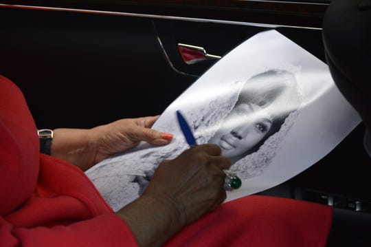 Aretha Franklin autographs a photo in June 2014.
