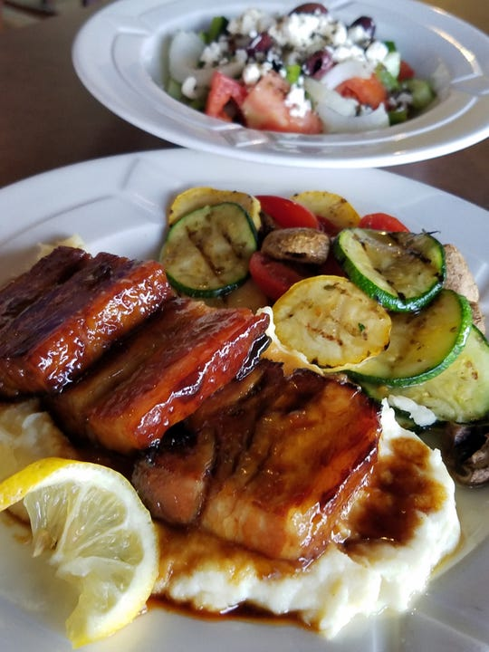 Here's what's causing all the fuss — slabs of slow-roasted pork belly in a sweet meaty glaze, served over mashed potatoes with colorful fresh veggies on the side. To the rear, a chunky Greek village salad.