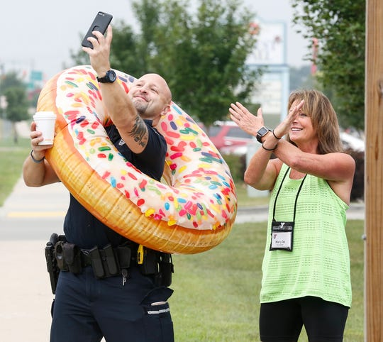 Fond du Lac Police Department officer Jesse Pimental and Mary Jo Neumann of the Fond du Lac Family YMCA take a selfie Friday in front of Dunkin Donuts on West Johnson Street in Fond du Lac during the Cop on a Rooftop event.
